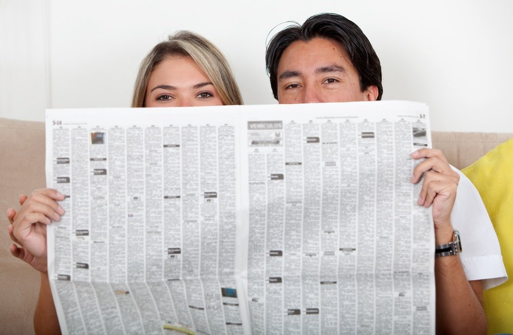 Couple covering their faces with a newspaper
