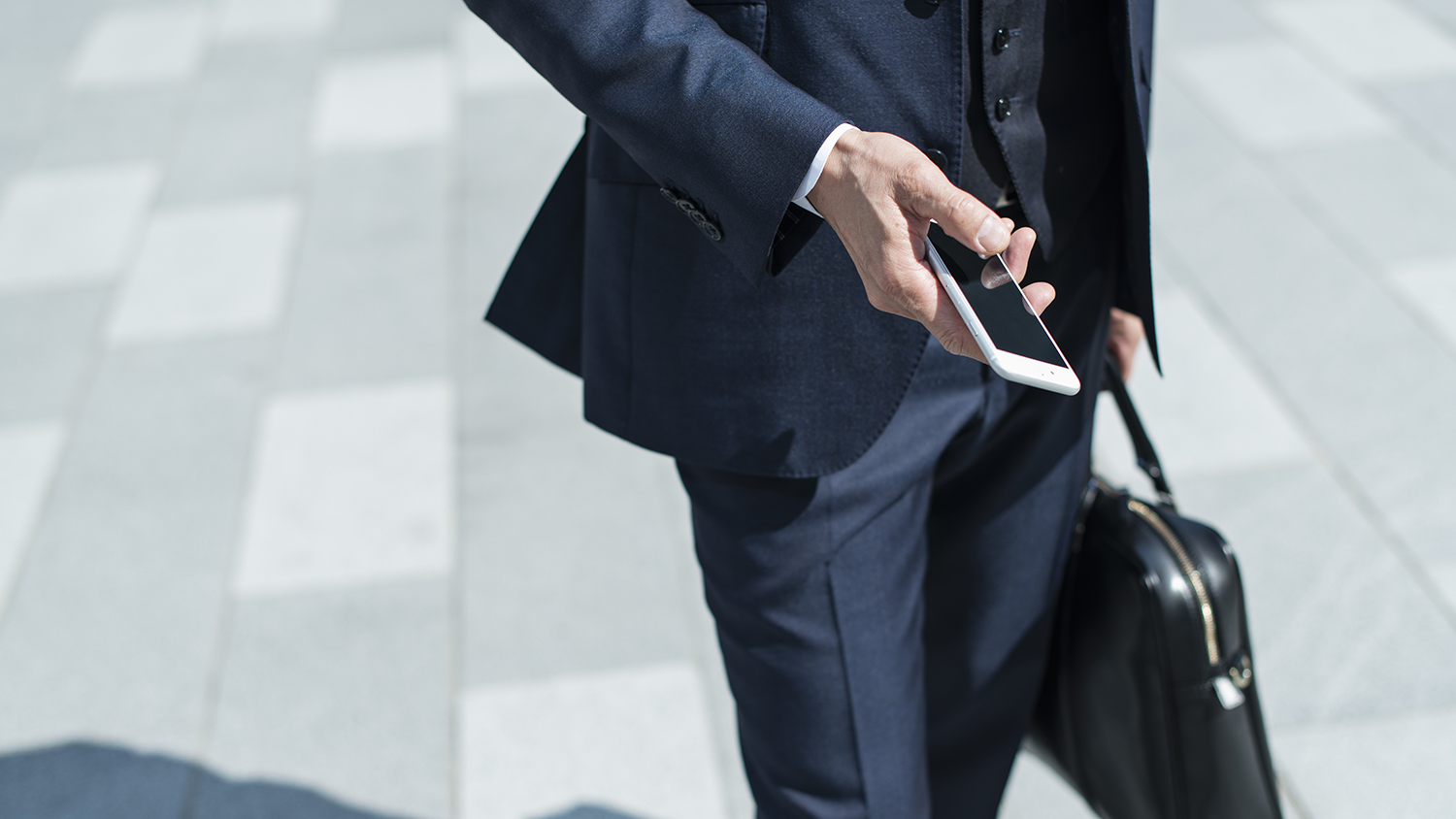 IT sales executive walking outside answering emails on smartphone