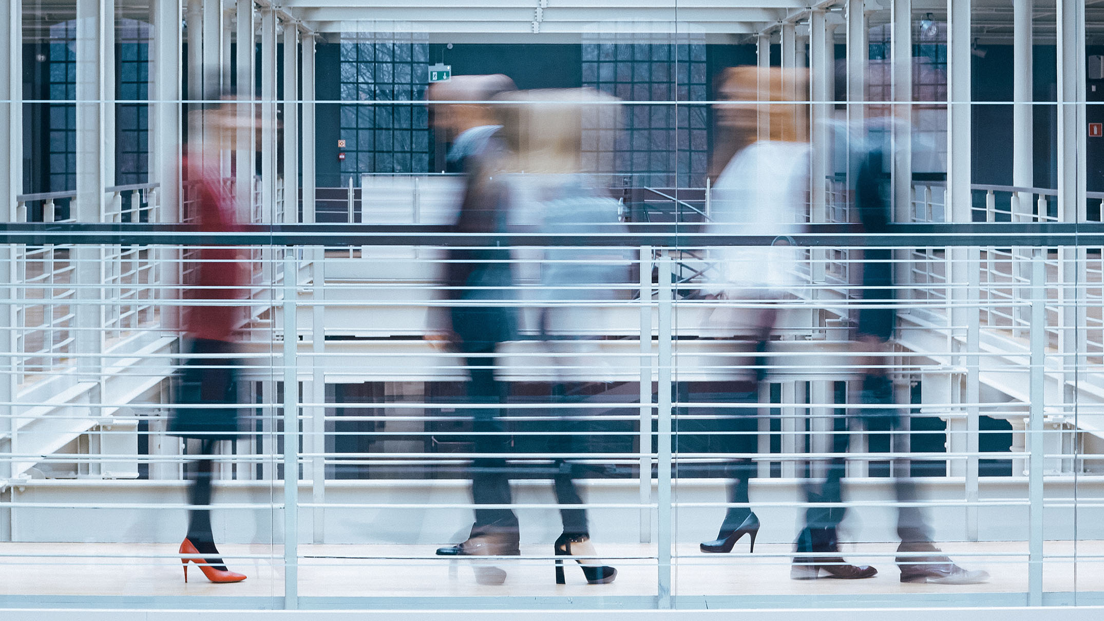 Blurry image of fast moving office workers in modern building